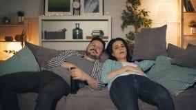 Homem cansado e sonolento e mulher dos povos que olham a tevê em casa no sofá que boceja