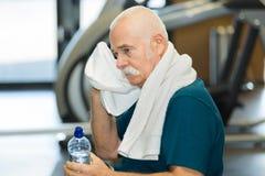 Homem cansado idoso no gym com toalha Imagens de Stock Royalty Free