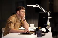 Homem cansado ou furado que trabalha tarde no escrit?rio da noite fotografia de stock