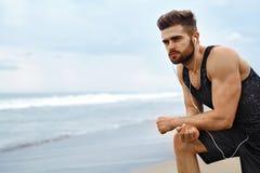 Homem cansado que descansa após a corrida na praia Os esportes malham exterior foto de stock royalty free