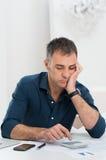 Homem cansado que faz cálculos Fotografia de Stock