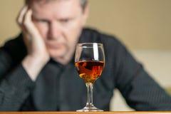 Homem cansado que inclina sua cabeça em um vidro da aguardente Homem fora de foco foto de stock