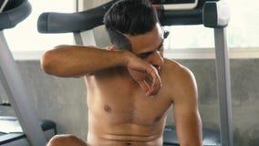 Homem cansado que limpa o suor ao relaxar após o exercício no gym filme