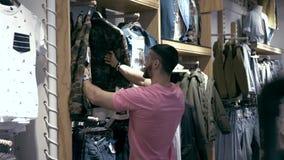 Homem caucasiano à moda novo que escolhe a roupa no shopping filme