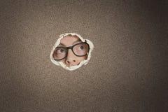 Homem caucasiano adulto meados de que olha longe do furo de papel rasgado Foto de Stock