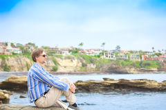Homem caucasiano, anos quarenta meados de que sentam-se pelo penhasco rochoso perto da água Fotos de Stock Royalty Free