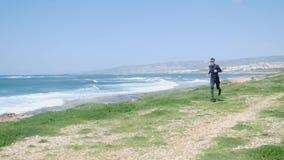 Homem caucasiano apto dos jovens que corre na praia que veste o equipamento e ?culos de sol pretos O mar ondulado est? no fundo filme