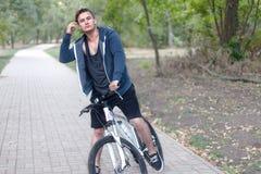Homem caucasiano considerável com monóculo redondo e os fones de ouvido que bicycling no parque fotos de stock
