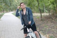 Homem caucasiano considerável com monóculo redondo e os fones de ouvido que bicycling no parque foto de stock