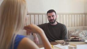 Homem caucasiano considerável na frente da mulher que fala ao apreciar a conversação no café filme