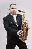 Homem caucasiano de relaxamento que levanta com o saxofone contra o fundo branco imagem de stock