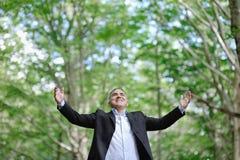 Homem caucasiano de sorriso em uma floresta - o sucesso relaxa o conceito da liberdade Foto de Stock
