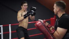 Homem caucasiano descamisado nas camisas pretas que treinam no gym O msn novo treina seus pés trabalhando com as patas, batendo b video estoque