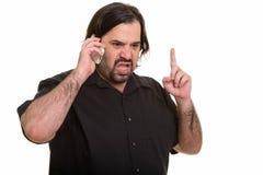Homem caucasiano gordo irritado que fala no telefone celular ao apontar f fotos de stock