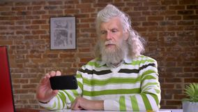 Homem caucasiano idoso engraçado com cabelo longo branco impressionante e barba em tomar selfies ao sentar-se no desktop em ocasi vídeos de arquivo
