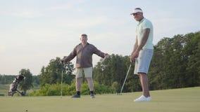 Homem caucasiano maduro e homem do Oriente Médio novo que joga o golfe no campo do golfe O indivíduo faz um perfurador e retroced vídeos de arquivo