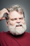 Homem caucasiano maduro que risca sua cabeça como esqueceu Somethin Fotografia de Stock
