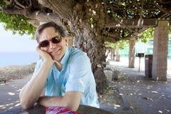 Homem caucasiano nos anos quarenta que relaxam sob o dossel de árvore protegida Imagens de Stock Royalty Free
