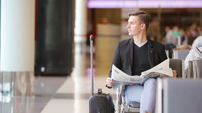 Homem caucasiano novo com o jornal no aeroporto ao esperar o embarque Terno vestindo do homem de negócios novo ocasional video estoque
