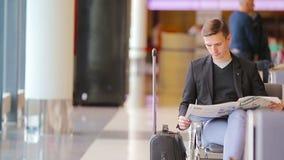 Homem caucasiano novo com o jornal no aeroporto ao esperar o embarque Terno vestindo do homem de negócios novo ocasional vídeos de arquivo