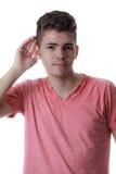Homem caucasiano novo com sua mão a sua orelha fotos de stock royalty free
