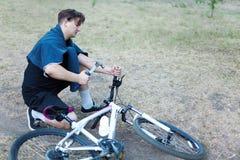 Homem caucasiano novo com trabalhos do cabelo escuro com o martelo à bicicleta colocada na terra no parque abandonado Divertiment imagem de stock royalty free