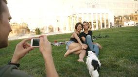 Homem caucasiano novo com um smartphone que toma a imagem de seus dois amigos fêmeas bonitos as meninas estão sentando-se no verd vídeos de arquivo