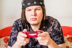 Homem caucasiano novo concentrado com os dreadlocks que sentam-se no sofá que joga jogos de vídeo fotografia de stock