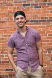 Homem caucasiano novo considerável com telefone celular e para trás chapéu que sorri para retratos na frente de parede de tijolo  imagens de stock