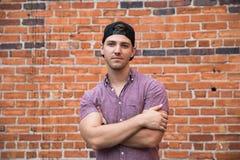 Homem caucasiano novo considerável com telefone celular e para trás chapéu que sorri para retratos na frente de parede de tijolo  imagem de stock