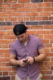 Homem caucasiano novo considerável com telefone celular e para trás chapéu que sorri para retratos na frente de parede de tijolo  foto de stock royalty free