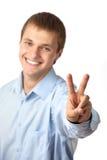 Homem caucasiano novo que mostra um sinal de paz Fotografia de Stock Royalty Free