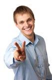 Homem caucasiano novo que mostra um sinal de paz Fotos de Stock Royalty Free