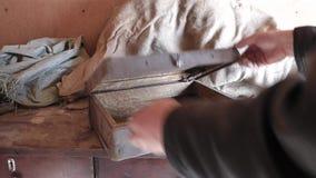 Homem caucasiano o caso empoeirado velho posto na tabela de madeira e abre-a filme