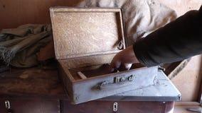 Homem caucasiano o caso empoeirado velho posto na tabela de madeira e abre-a video estoque