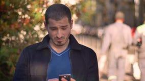 Homem caucasiano que olha em emoções em mudança do smartphone da indignação à satisfação no fundo outonal da rua video estoque