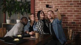 Homem caucasiano que toma o selfie do grupo em encontrar amigos diversos no coffeeshop ou no local de trabalho, jovem multirracia video estoque