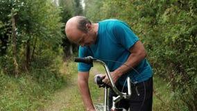 Homem caucasiano superior no t-shirt azul que tenta montar uma bicicleta filme