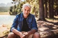 Homem caucasiano superior que relaxa em um log pelo lago Fotografia de Stock Royalty Free