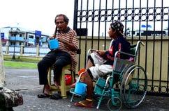 Homem cego ao lado do mendigo deficiente na cadeira de rodas no portal da porta da jarda da igreja para procurar a esmola fotos de stock royalty free