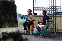 Homem cego ao lado do mendigo deficiente na cadeira de rodas no portal da porta da jarda da igreja para procurar a esmola fotos de stock
