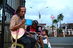 Homem cego ao lado do mendigo deficiente na cadeira de rodas no portal da porta da jarda da igreja para procurar a esmola foto de stock