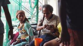Homem cego entre dois mendigos fêmeas no portal da igreja vídeos de arquivo