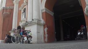 Homem cego, mendigos coxos na cadeira de rodas que imploram pela esmola no portal da fachada da igreja video estoque