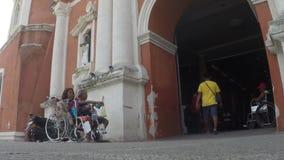 Homem cego, mendigos coxos na cadeira de rodas que imploram pela esmola no portal da fachada da igreja vídeos de arquivo