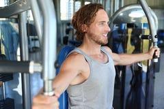 Homem center do Gym que dá certo na máquina da aptidão imagens de stock royalty free