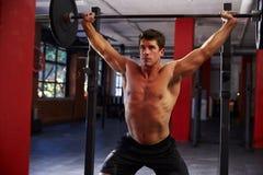 Homem Chested desencapado em levantar peso do Gym foto de stock