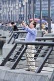 Homem chinês idoso que fotografa no bulevar da barreira, Shanghia, China fotografia de stock