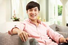 Homem chinês novo que relaxa no sofá em casa Imagens de Stock Royalty Free