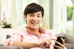 Homem chinês novo que usa o telefone móvel Fotografia de Stock Royalty Free